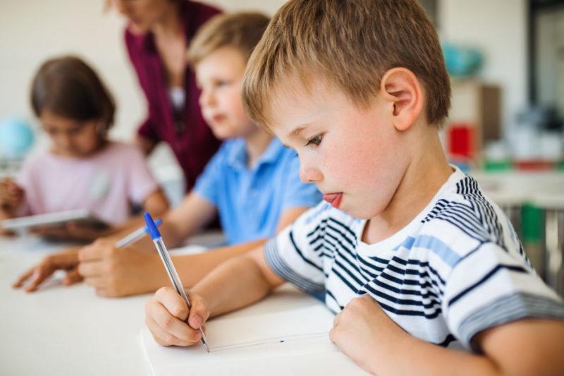Enfant qui se concentre pour écrire