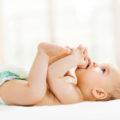 bébé sur le dos qui joue avec ses pieds