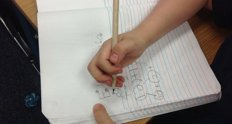 Un enfant écrit dans un cahier de vacances
