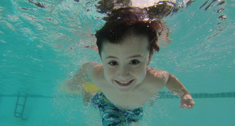 un niño sonríe bajo el agua
