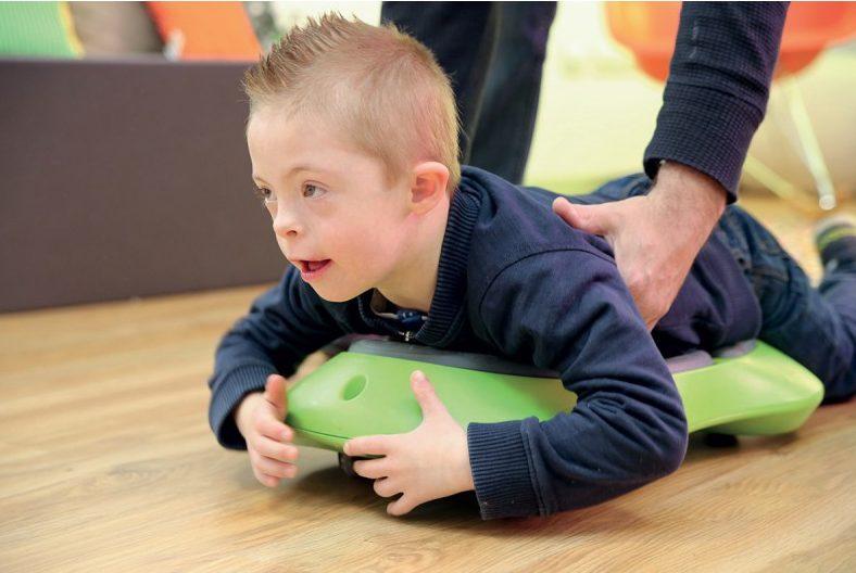 Enfant sur une planche tenu par un psychomotricien
