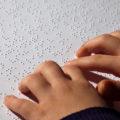 enfant qui lit un texte en braille UNE
