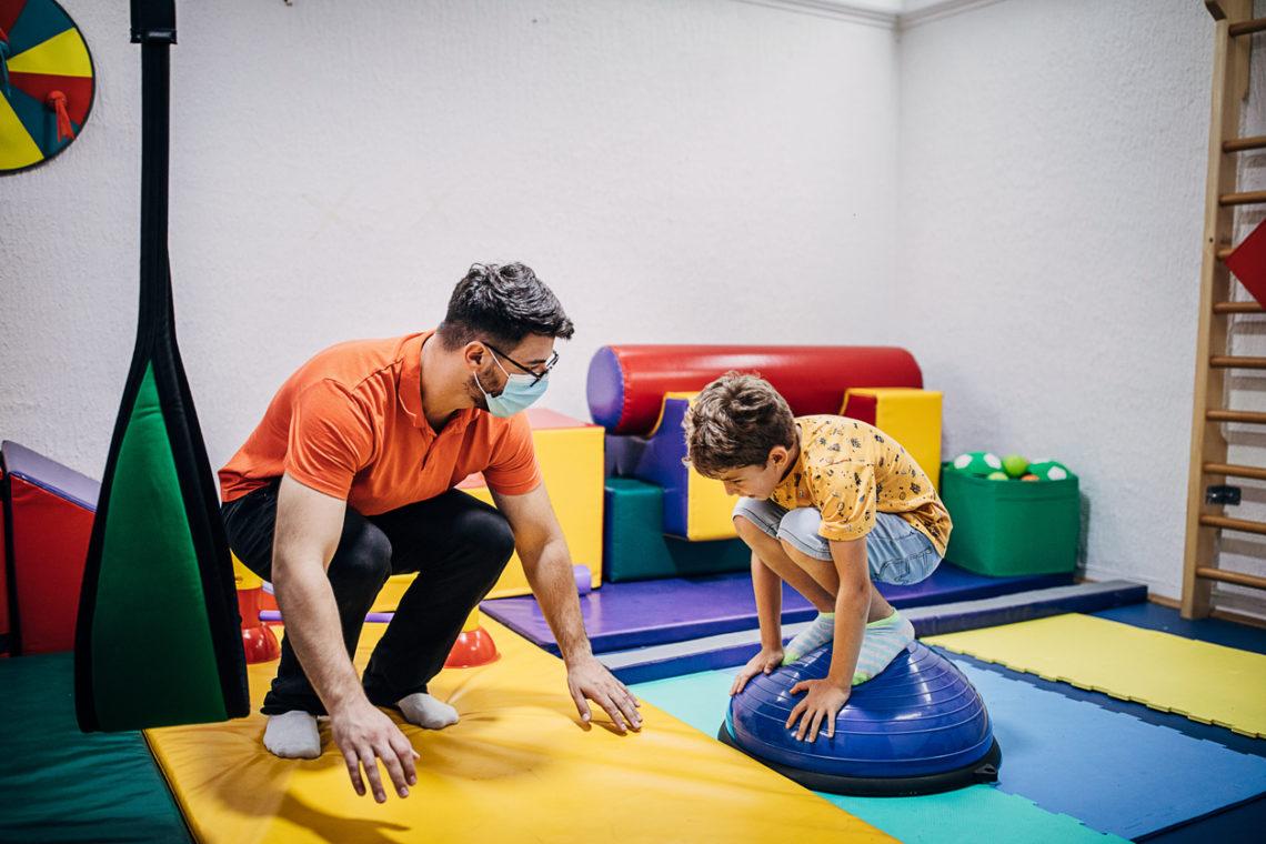 Enfant garçon qui s'exerce avec son psychomotricien Istock