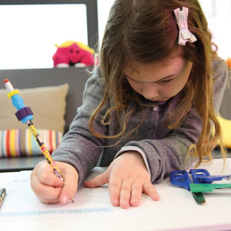 Un enfant écrit avec un crayon fidget sur une feuille
