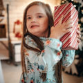 Enfant exceptionnelle avec un cadeau dans les mains à Noël