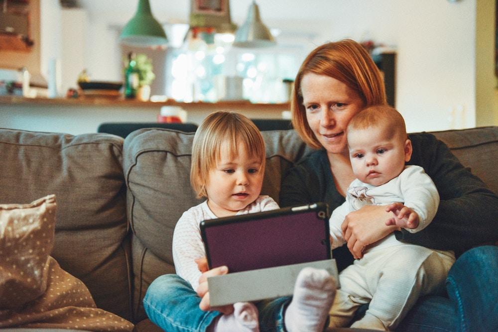 Une mère et ses deux enfants devant un écran de tablette.