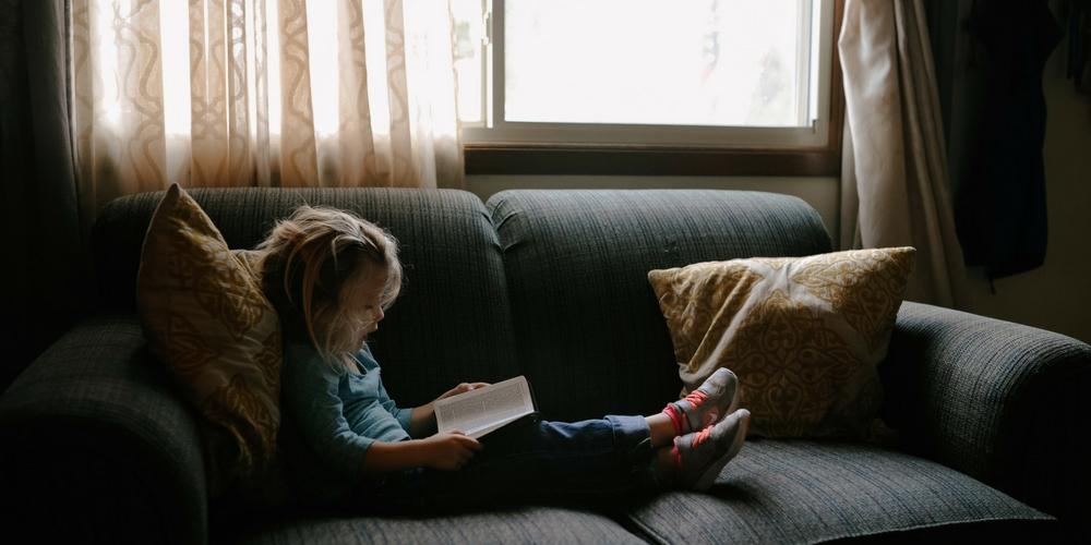 Une enfant lit sur le canapé