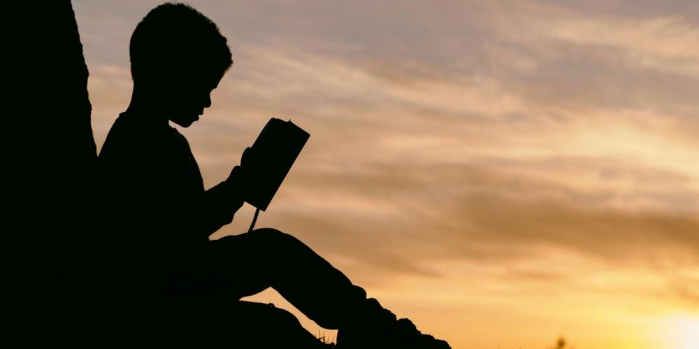 Un enfant lit un livre la nuit