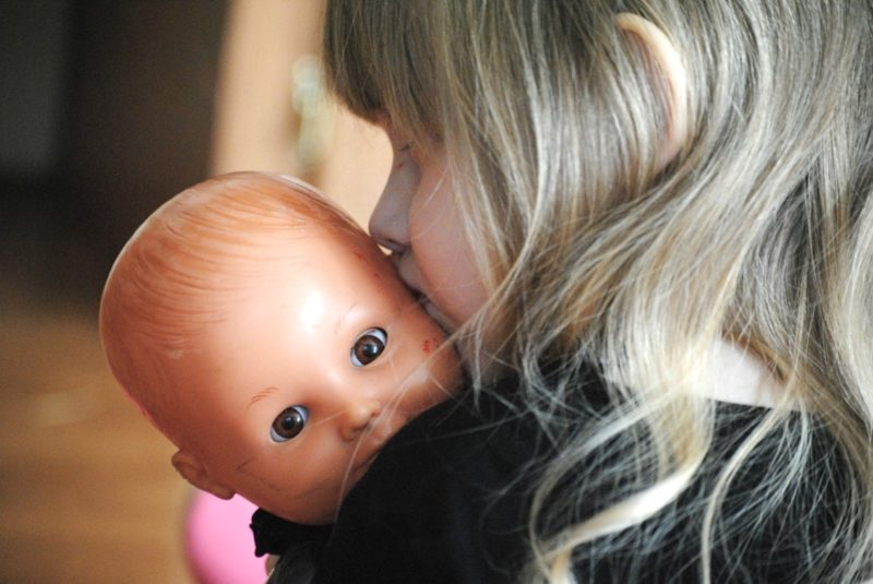 Niña besa su muñeca