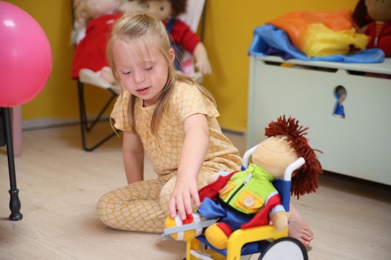 Niña con síndrome de down juega con un muñeco en silla de ruedas