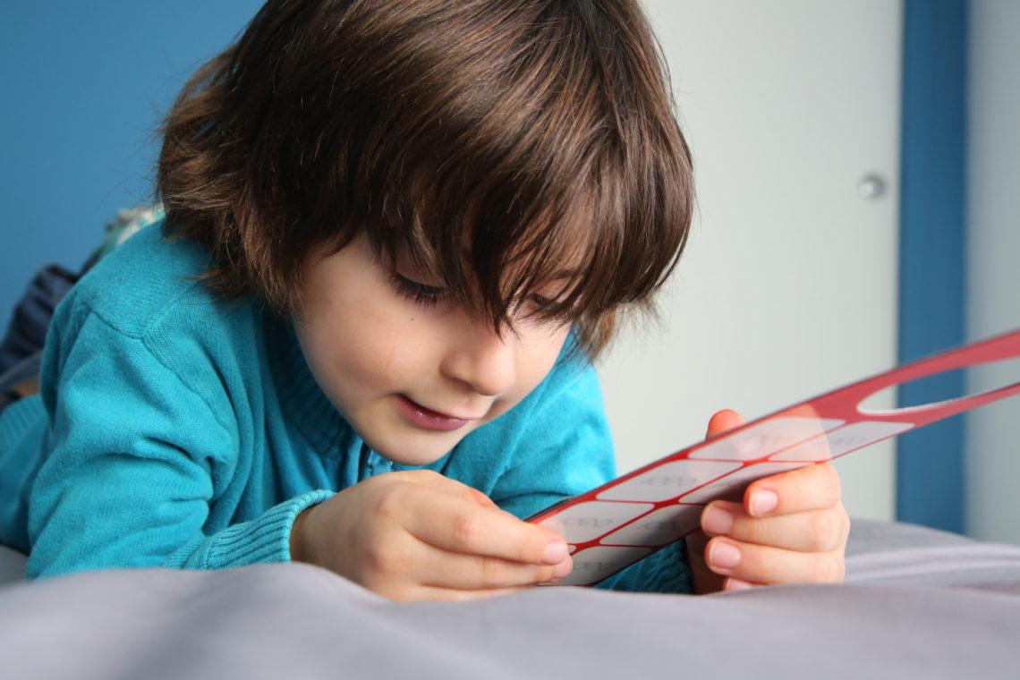 Un enfant tient dans sa main un support de communication pour pictogrammes aimantés Idéo Picto.