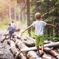 Enfant en équilibre sur rondin de bois dans la forêt. Petit aventurier