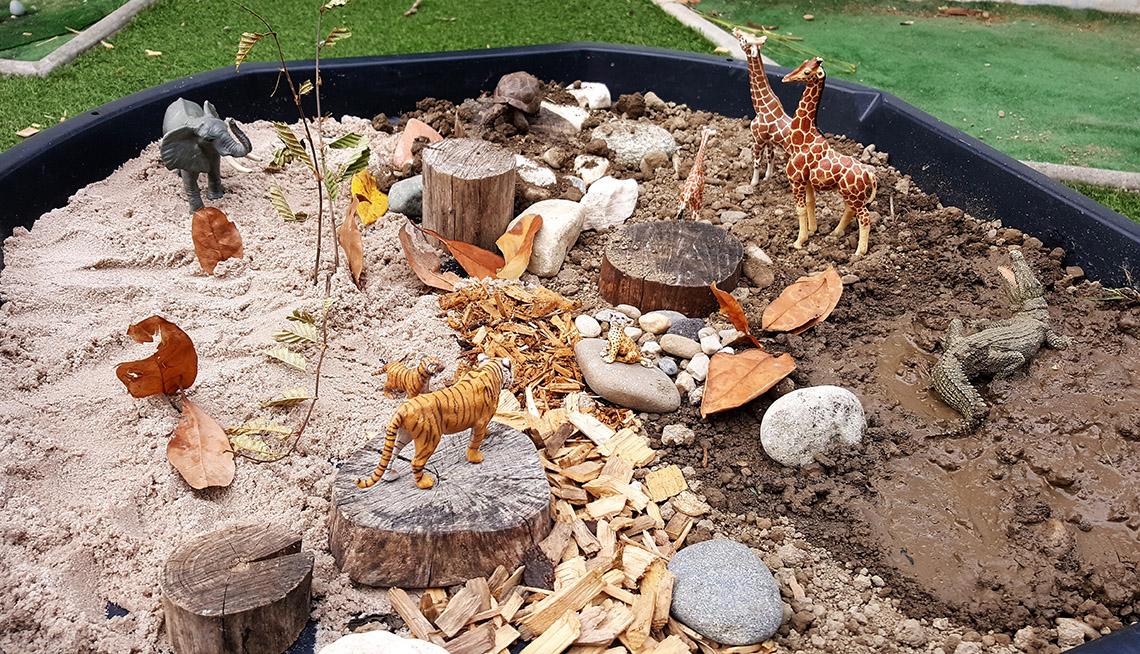 Une mise en scène avec des figurines d'animaux, du sable, du bois et de la terre