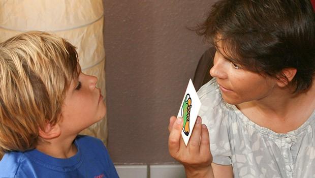 Langage : Une femme communique avec un enfant à l'aide d'un pictogramme représentant une chaussure.