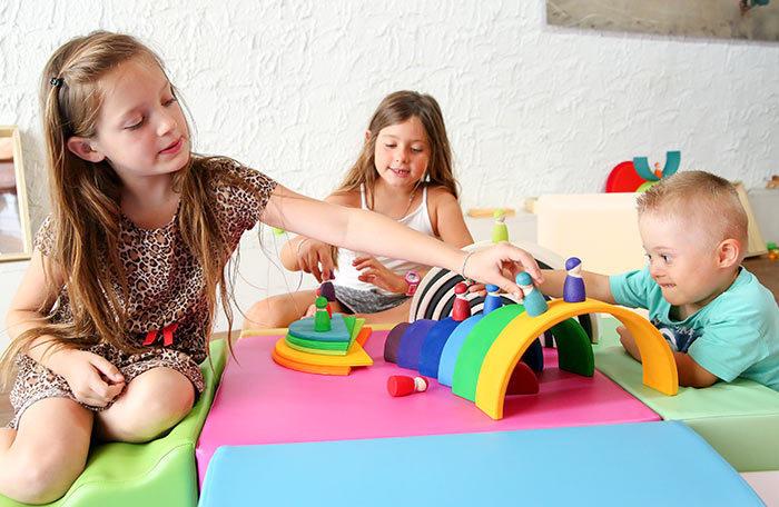 Des enfants jouent avec des jeux invitant à la libre exploration. Les arcs en bois de différentes couleurs deviennent des ponts.