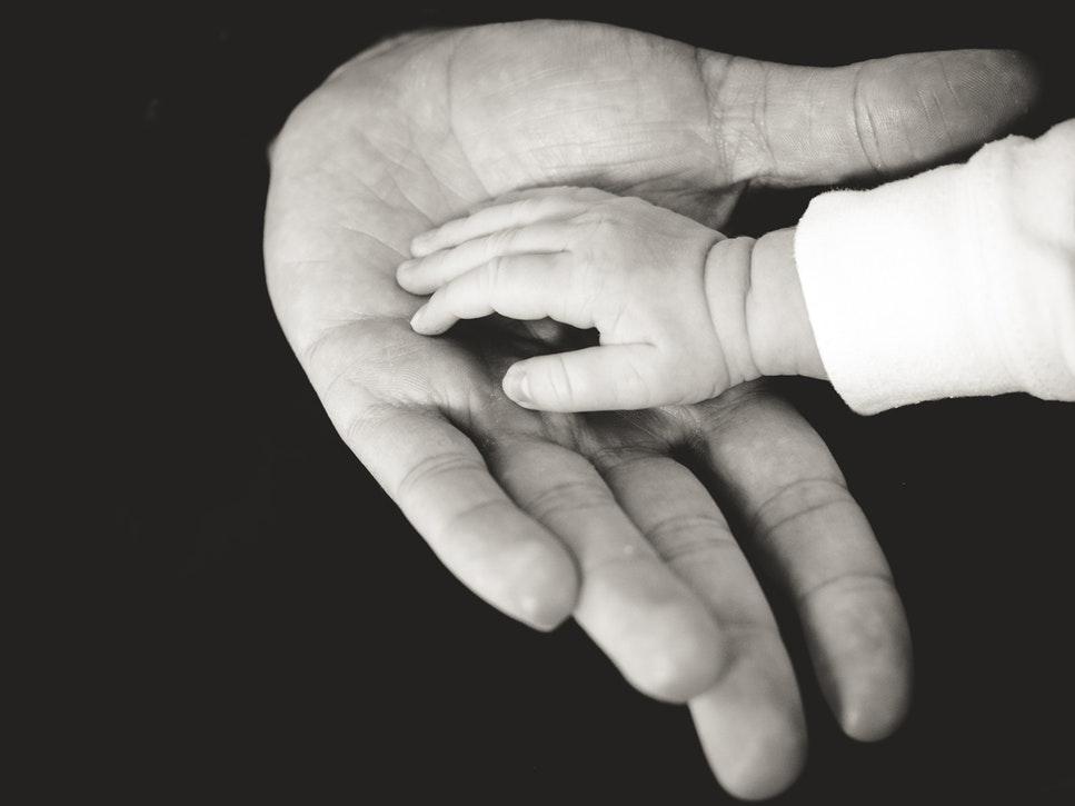 Photo en noir et blanc d'une petite main d'enfant dans une main d'adulte.