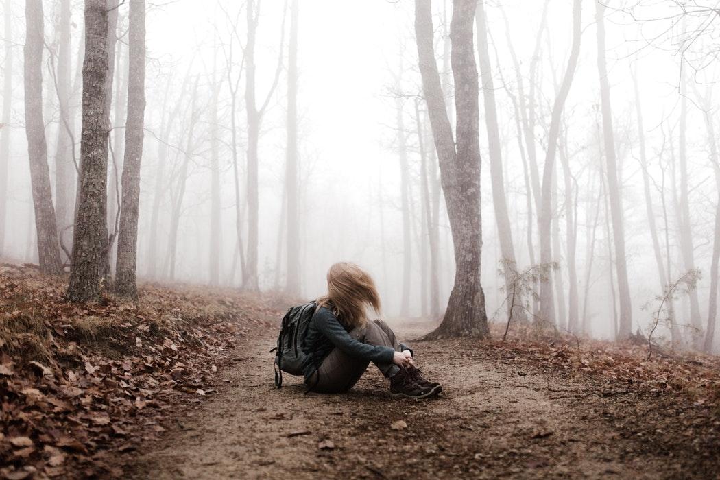 Jeune femme assise au sol dans la forêt. Elle est entourée de brouillard et ses cheveux sont dans son visage.