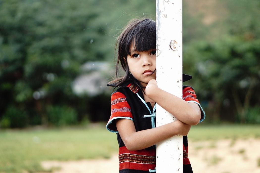 Enfant qui tient un poteau dans ses bras. Il a l'air triste.