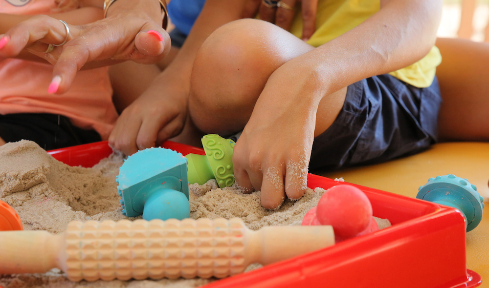 Bac de sable sensoriel rouge avec des accessoires (tampons, petit rouleur, etc.).