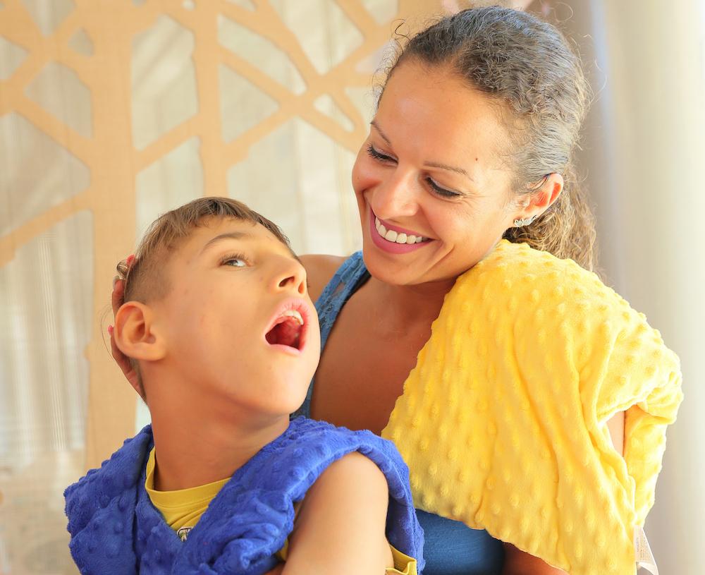 Enfant polyhandicapé qui teste différents coussins sensoriels.