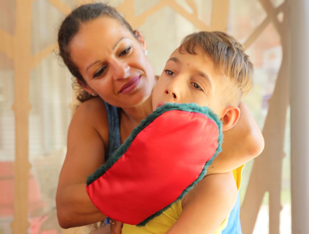 Enfant polyhandicapé qui se fait caresser la joue avec un gant sensoriel.