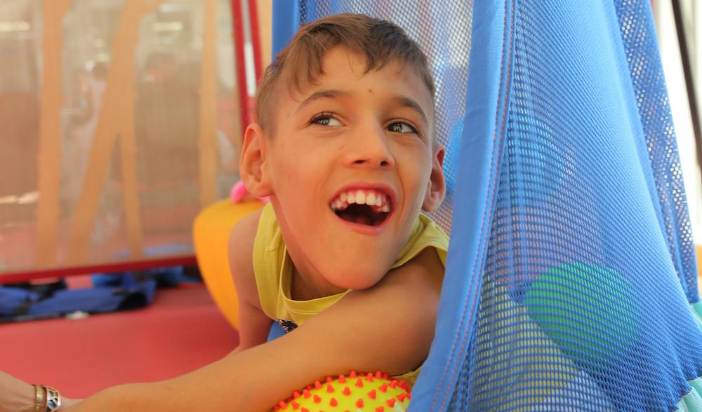 Enfant polyhandicapé qui est assis dans un nid hamac.