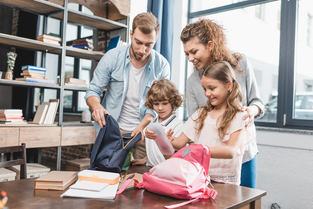 Des parents préparent les sacs pour l'école avec leurs enfants pour la rentrée