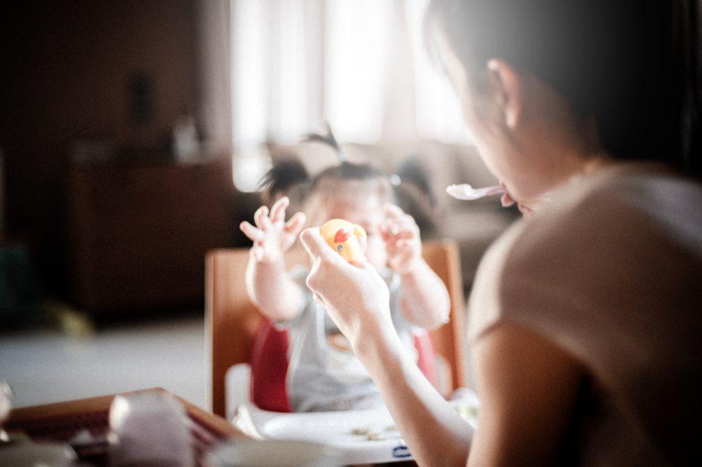 Une maman tient un jouet et une cuillère devant un enfant