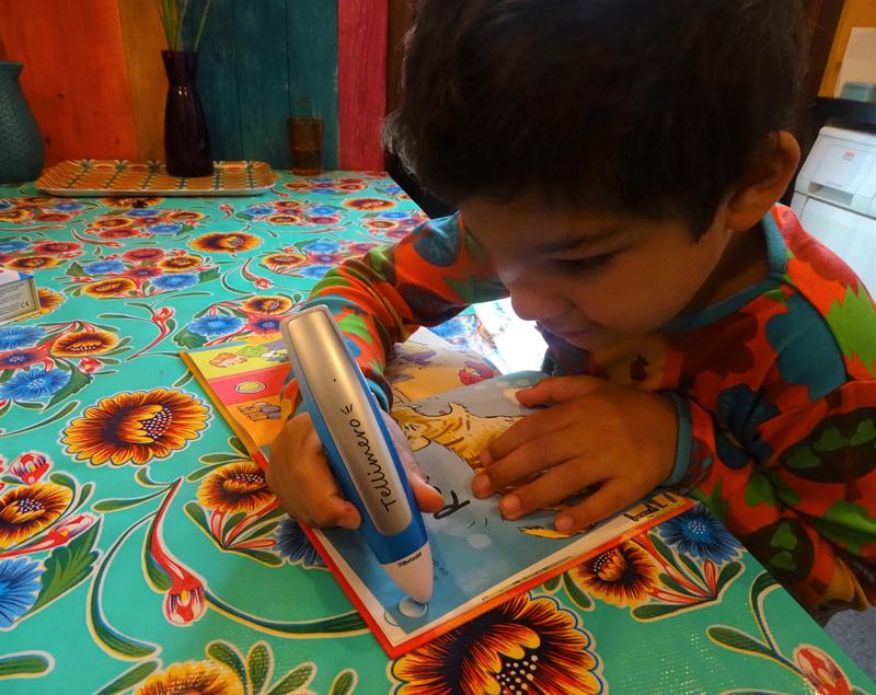Milo qui lit une histoire en passant son tellimero sur une pastille placée sur la page de son livre.