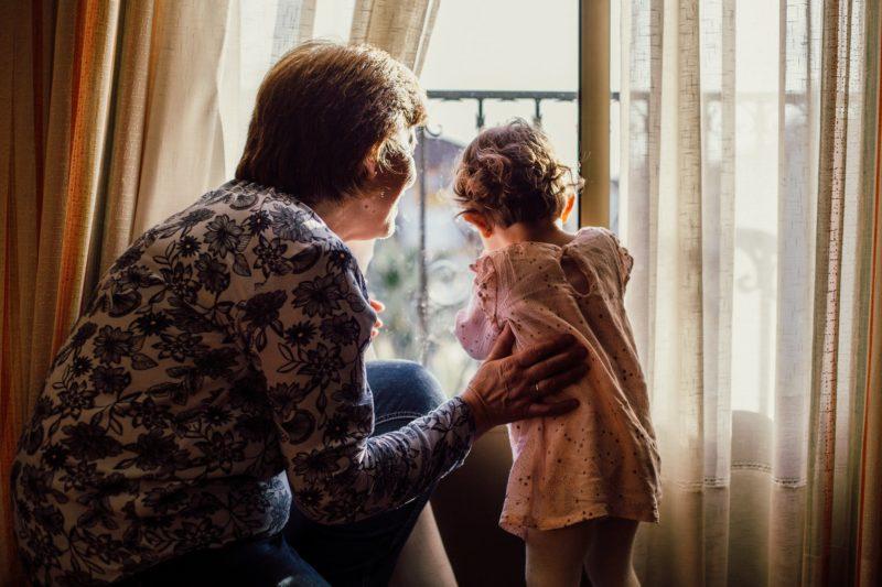 Une personne âgée avec une petite fille qui regardent par la fenêtre.