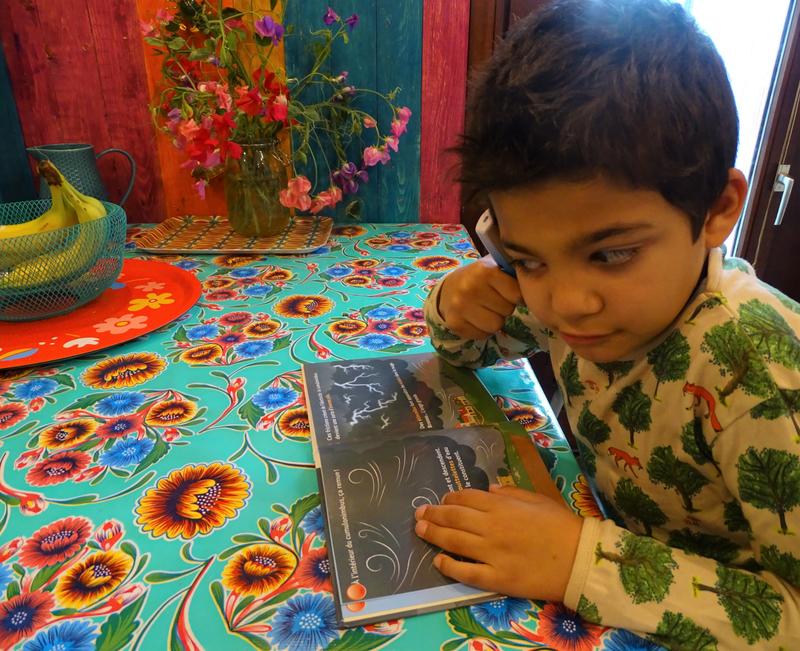 Milo qui lit un livre grâce à son Tellimero.