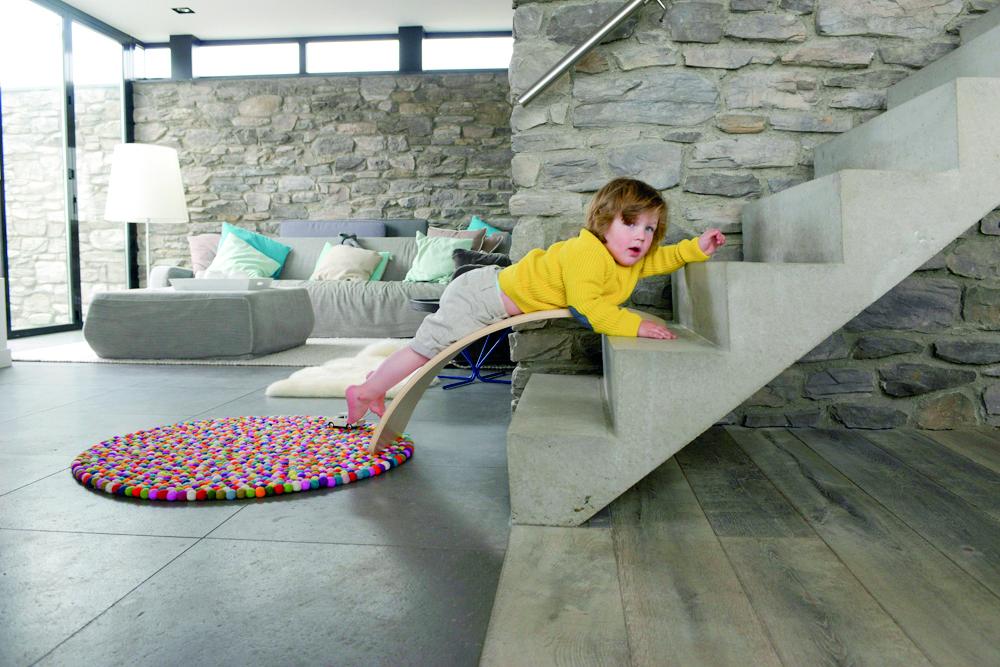 Un enfant qui est allongé sur une planche Wobbel en bas d'un escalier.