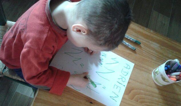 Un enfant trace des lettres