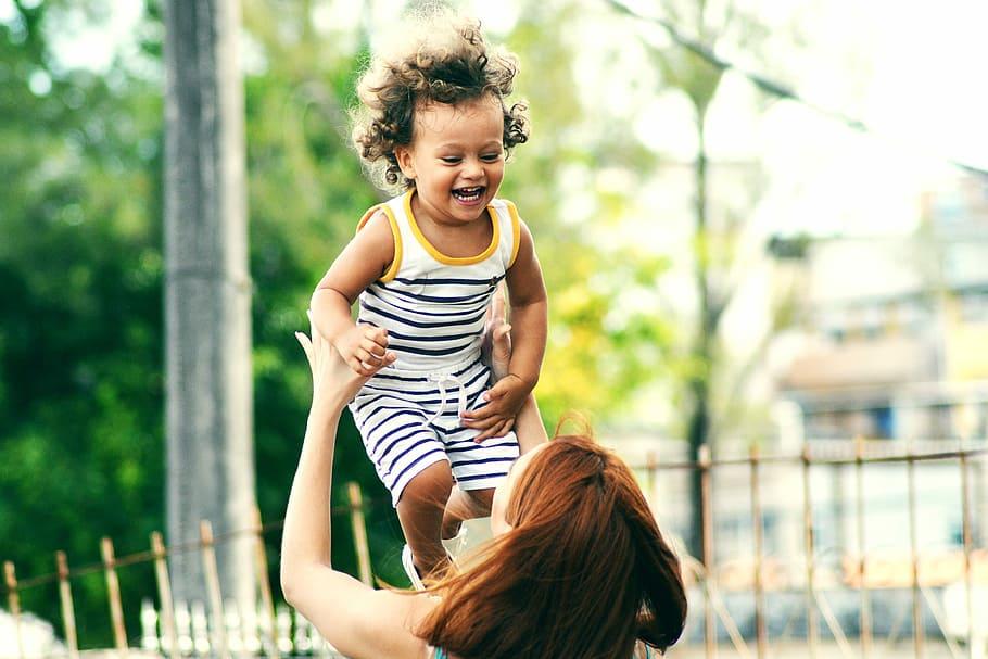 Une maman lance dans les airs un jeune enfant qui rit.