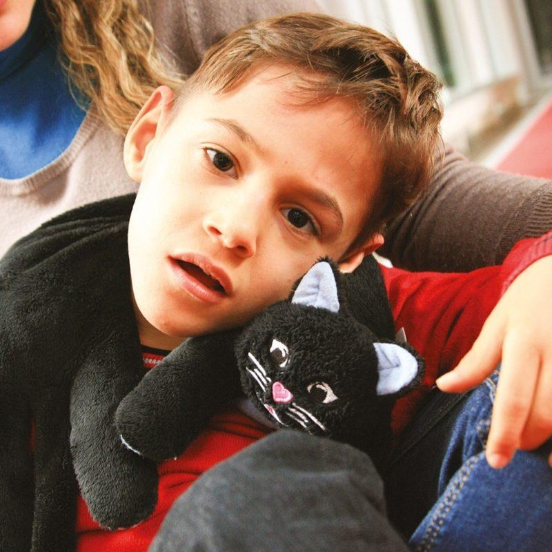 Enfant avec un produit lesté autour du cou : le chat lesté.