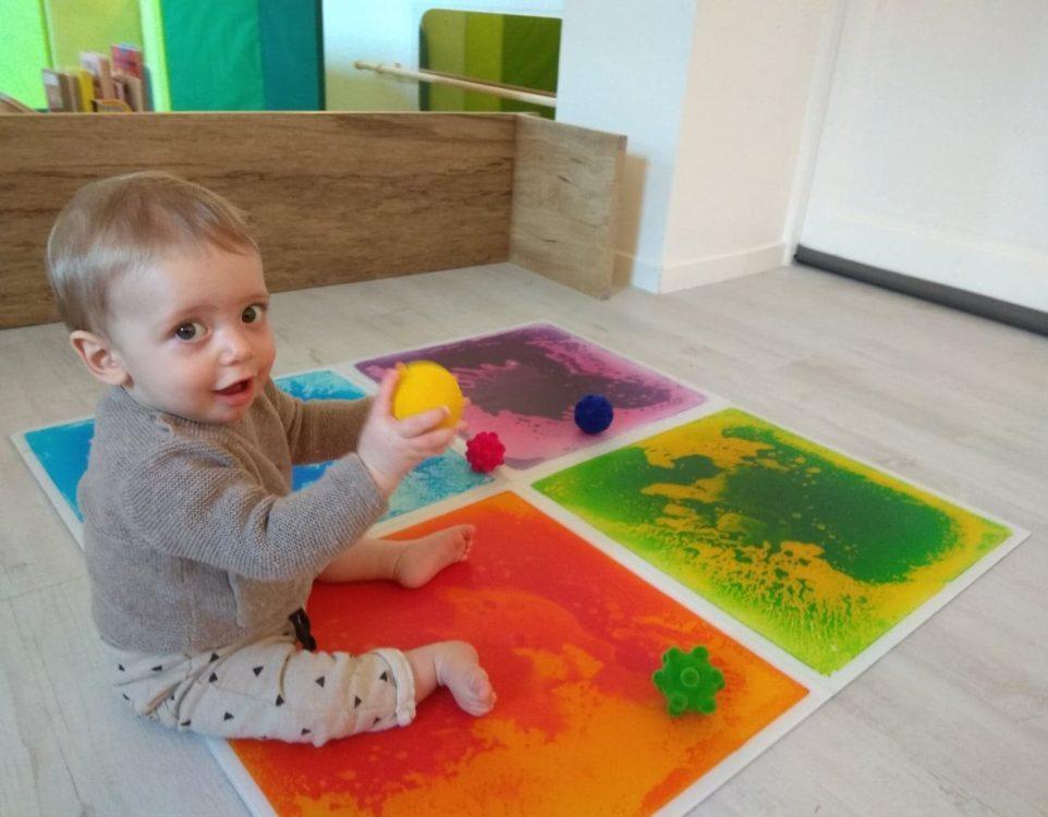 Jeune enfant assis sur des plaques sensori-motrices et qui tient une balle jaune dans ses mains.