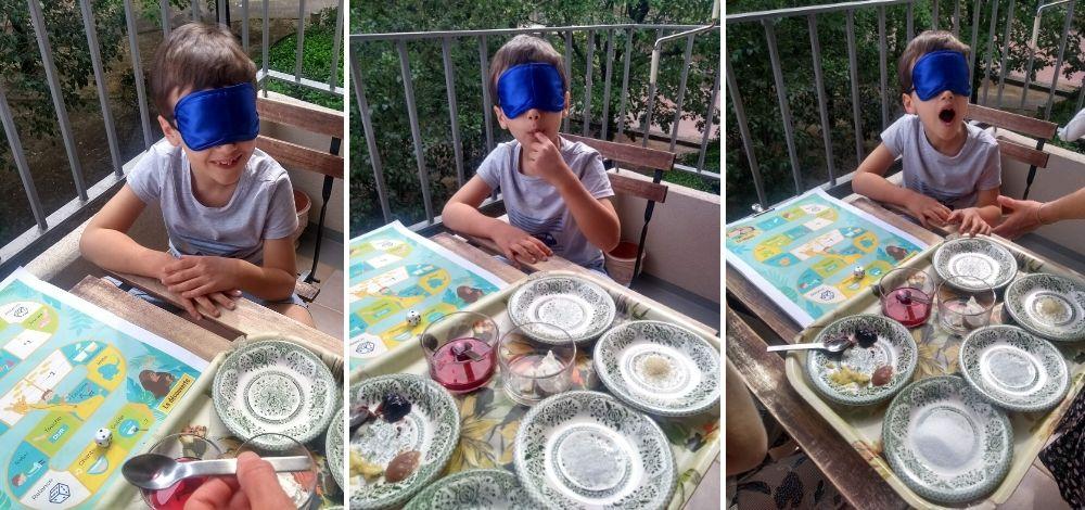 Un enfant, qui a les yeux bandés, goûte à diverses saveurs présentées dans des assiettes devant lui.