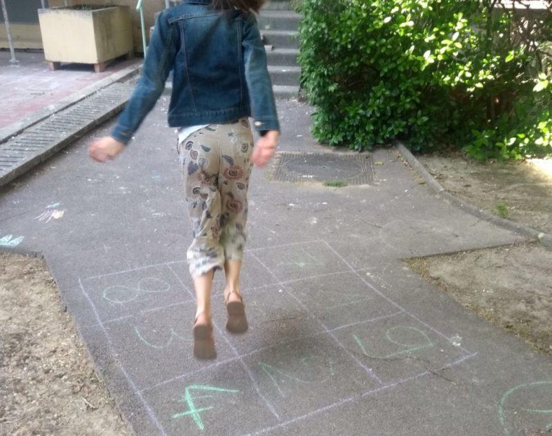 Enfant qui saute sur un cadran numérique dessiné à la craie sur le sol