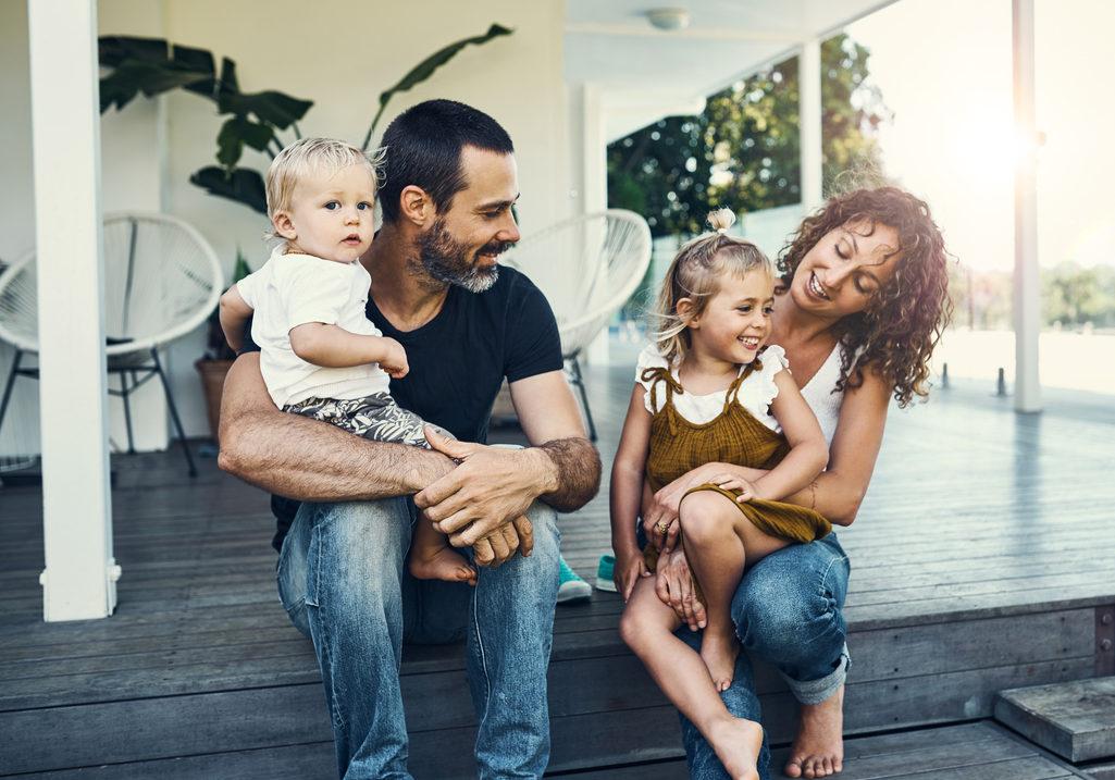 Famille assise devant une maison sur des marches.
