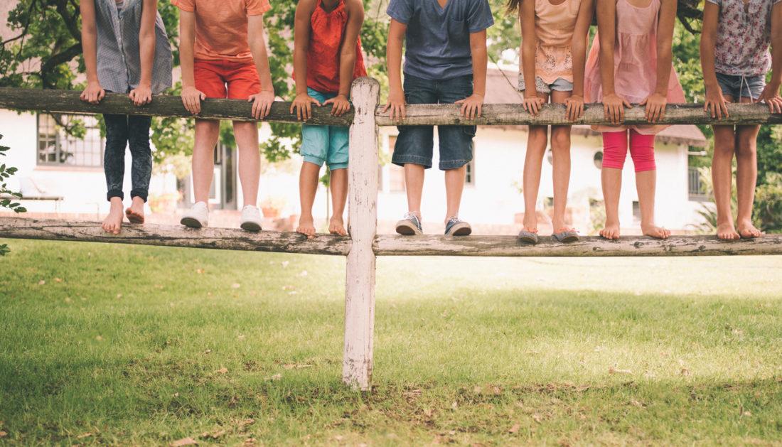 Enfants sur une barrière en bois