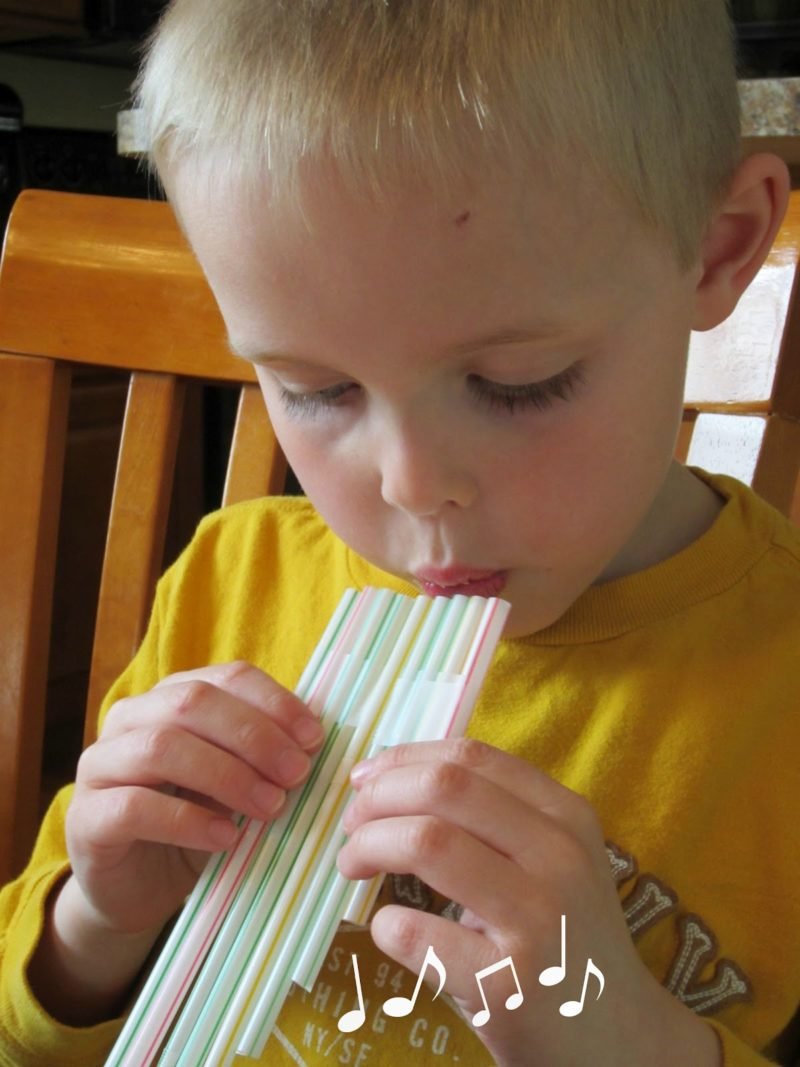 Un enfant joue d'une flûte de pan faites avec des pailles.