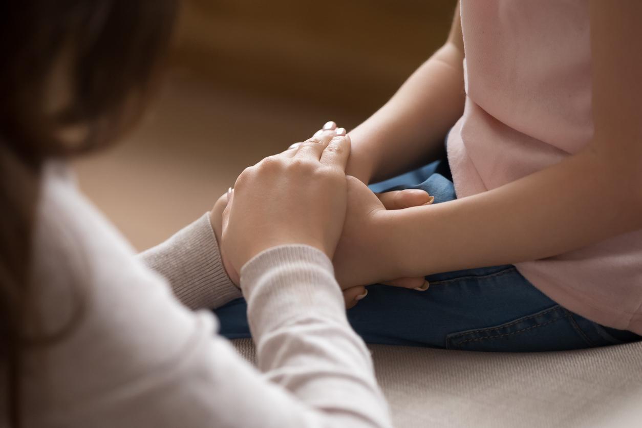 Un adulte qui tient les mains d'un enfant de façon protectrice.