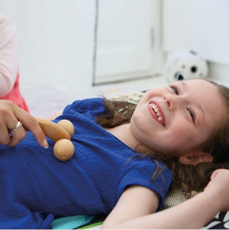 Une enfant polyhandicapé reçoit un massage grâce à un outils du panier de massage