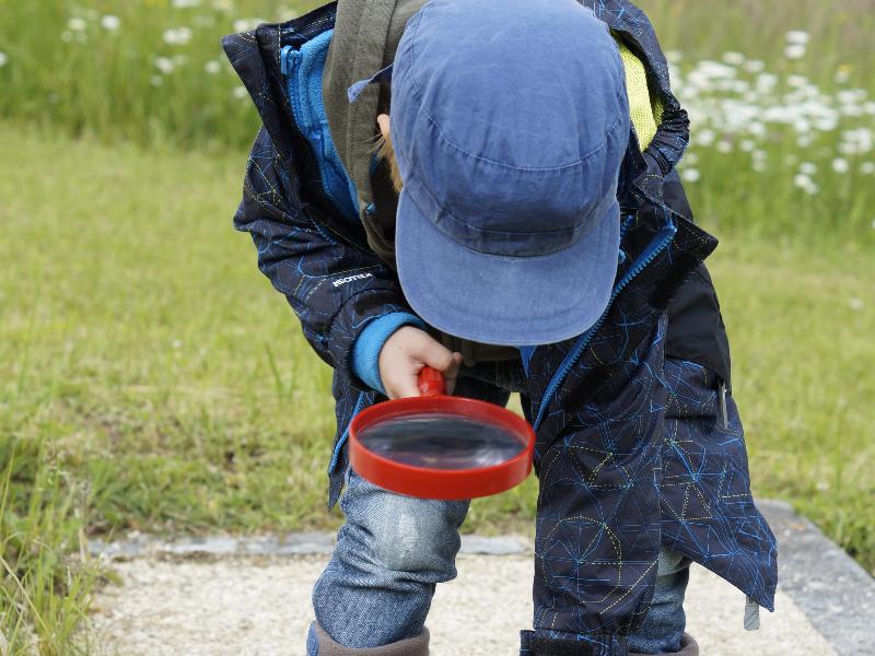 Un enfant joue avec une loupe à l'extérieur