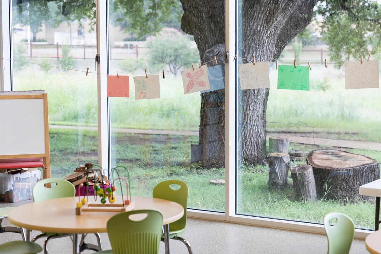 Salle de classe aux grandes fenêtres qui donnent sur un extérieur verdoyant