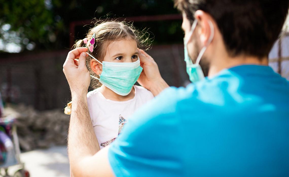 Un homme place un masque sur le visage d'une petite fille.