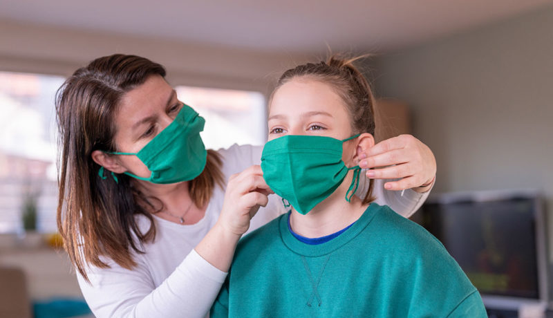 Une mère aide son enfant à placer son masque sur son visage
