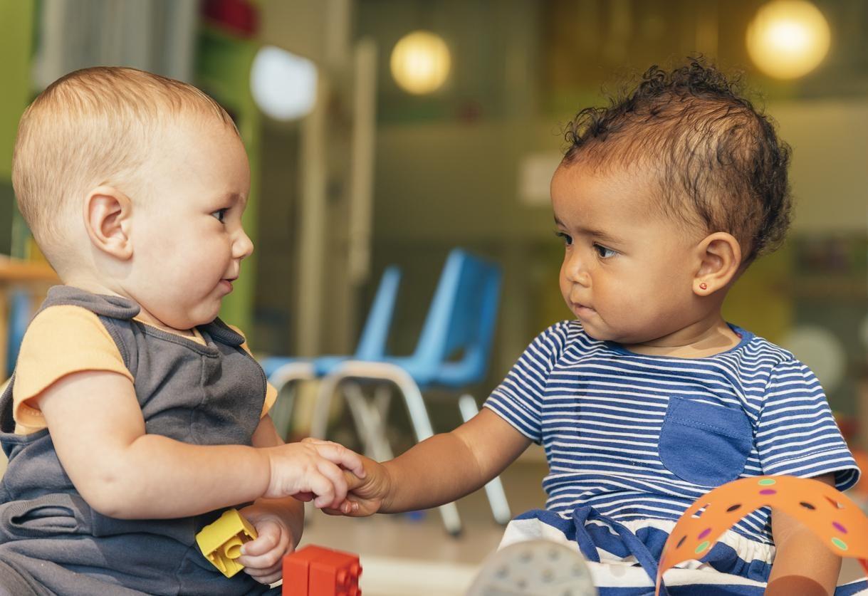 Deux bébés se tenant par la main.