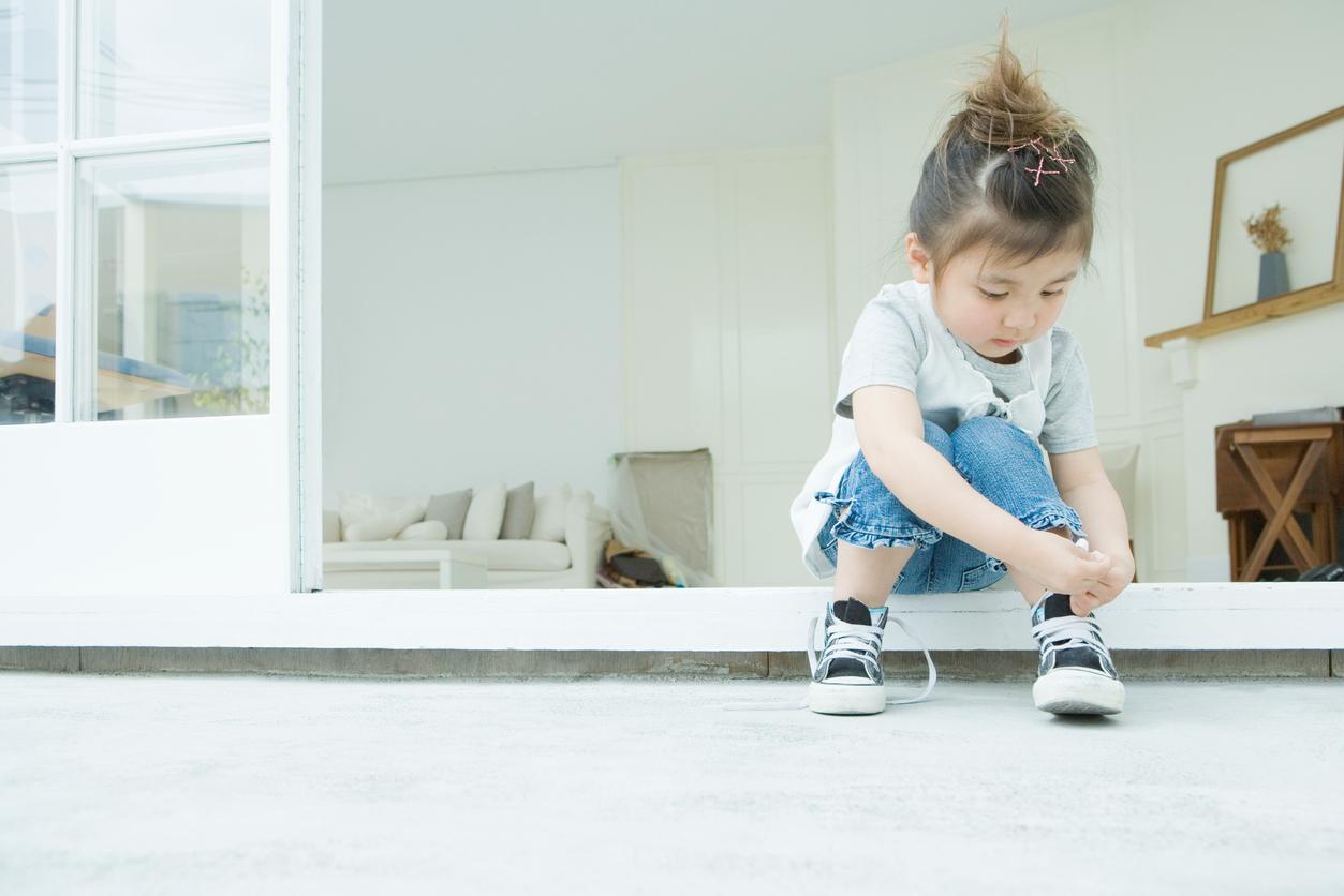 Une enfant met ses chaussures toute seul