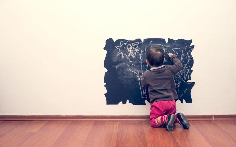 enfant qui écrit sur le mur